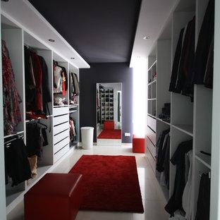 Réalisation d'un grand dressing room design pour une femme avec un placard sans porte et des portes de placard blanches.
