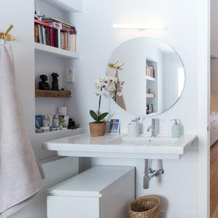 Imagen de aseo actual, pequeño, con armarios con paneles lisos, puertas de armario blancas, paredes blancas, suelo de madera en tonos medios, lavabo suspendido y suelo marrón