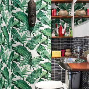 Foto de aseo exótico, pequeño, con sanitario de dos piezas, paredes multicolor, baldosas y/o azulejos negros, lavabo encastrado y suelo gris
