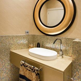 Moderne Gästetoilette mit flächenbündigen Schrankfronten, beigen Schränken, farbigen Fliesen, Mosaikfliesen, beiger Wandfarbe, Aufsatzwaschbecken, grauem Boden und beiger Waschtischplatte in Sevilla