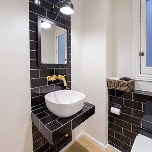 Exemple d'un petit WC et toilettes tendance avec des carreaux de céramique, un mur blanc, un plan de toilette en bois, un WC suspendu, un carrelage noir, un sol en bois brun, un lavabo suspendu et un plan de toilette noir.