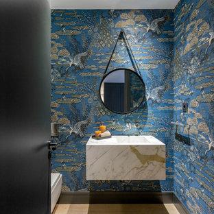 Foto de aseo flotante y papel pintado, contemporáneo, papel pintado, con paredes azules, suelo de madera en tonos medios, suelo marrón, encimeras blancas y papel pintado