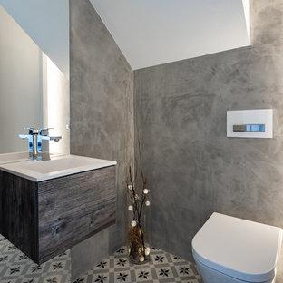 Ejemplo de aseo nórdico, grande, con armarios con paneles lisos, suelo de azulejos de cemento, suelo multicolor, puertas de armario de madera en tonos medios, sanitario de pared, paredes grises, lavabo integrado y encimeras blancas