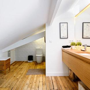 Inspiration pour un WC et toilettes nordique de taille moyenne avec un placard à porte plane, des portes de placard en bois brun, un WC séparé, un mur blanc, un sol en bois brun, un lavabo encastré, un plan de toilette en bois, un sol marron, un carrelage blanc et un plan de toilette marron.
