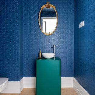 Diseño de aseo contemporáneo con paredes azules, suelo de madera en tonos medios, lavabo sobreencimera y suelo marrón