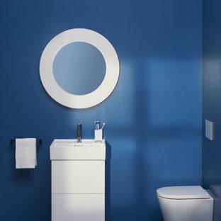 Modelo de aseo minimalista, de tamaño medio, con armarios tipo mueble, puertas de armario blancas, urinario, paredes azules, lavabo integrado y encimeras blancas
