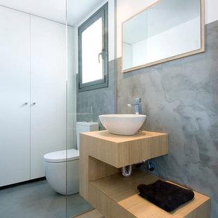 Modelo de aseo actual, pequeño, con armarios con paneles lisos, puertas de armario de madera clara, paredes grises, suelo de cemento, lavabo sobreencimera, encimera de madera, suelo gris y encimeras beige