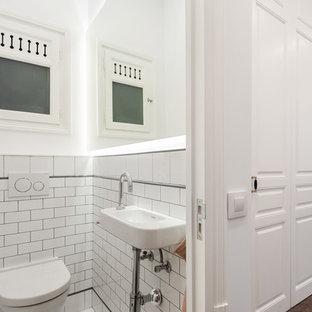 Modelo de aseo clásico con sanitario de pared, baldosas y/o azulejos blancos, baldosas y/o azulejos de cemento, paredes blancas y lavabo suspendido