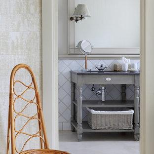 Imagen de aseo tradicional, de tamaño medio, con armarios tipo mueble, puertas de armario grises, baldosas y/o azulejos blancos, baldosas y/o azulejos de cerámica, paredes blancas, suelo de cemento y suelo beige