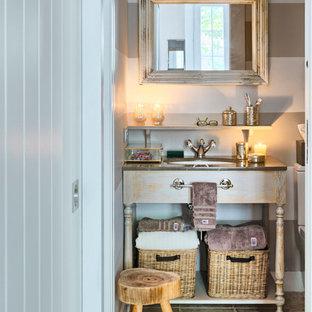 Пример оригинального дизайна: маленький туалет в скандинавском стиле с фасадами островного типа, светлыми деревянными фасадами, разноцветными стенами, полом из терракотовой плитки, врезной раковиной и столешницей из искусственного камня