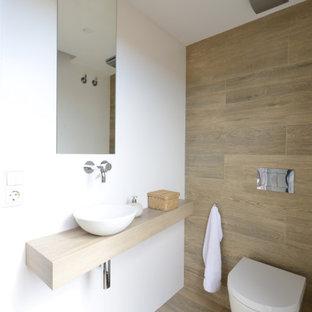 Imagen de aseo contemporáneo, de tamaño medio, con baldosas y/o azulejos beige, baldosas y/o azulejos de porcelana, paredes blancas, suelo de baldosas de porcelana, lavabo sobreencimera, encimera de madera, suelo beige y encimeras beige