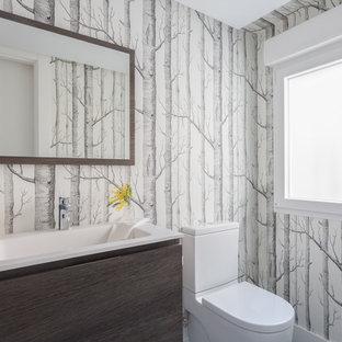 Modelo de aseo actual con armarios con paneles lisos, puertas de armario de madera en tonos medios, sanitario de dos piezas, lavabo integrado, encimeras blancas y paredes multicolor