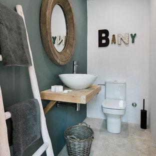 Idées déco pour un petit WC et toilettes montagne avec un mur multicolore, béton au sol, une vasque, un plan de toilette en bois, un sol gris et un plan de toilette beige.