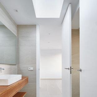 Ejemplo de aseo actual, de tamaño medio, con armarios abiertos, puertas de armario de madera oscura y lavabo sobreencimera