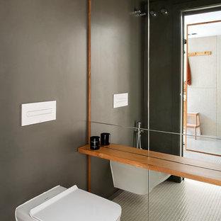 Пример оригинального дизайна: большой туалет в современном стиле с унитазом-моноблоком, зеленой плиткой, керамической плиткой, зелеными стенами и зеленым полом
