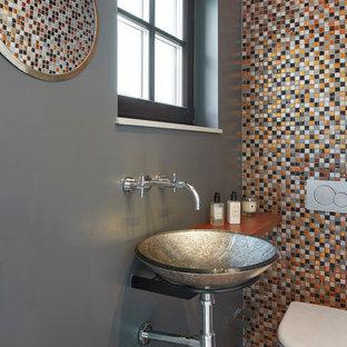 Imagen de aseo contemporáneo con baldosas y/o azulejos multicolor, baldosas y/o azulejos en mosaico, paredes grises, lavabo sobreencimera, encimera de madera, encimeras marrones y sanitario de pared