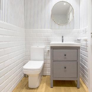 Foto de aseo escandinavo con armarios tipo mueble, puertas de armario grises, baldosas y/o azulejos blancos, baldosas y/o azulejos de cemento, paredes multicolor y suelo de madera clara