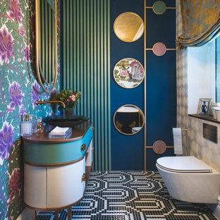 Diseño de aseo papel pintado, actual, grande, papel pintado, con armarios tipo mueble, puertas de armario blancas, sanitario de pared, paredes azules, lavabo sobreencimera, suelo multicolor, encimeras marrones y papel pintado