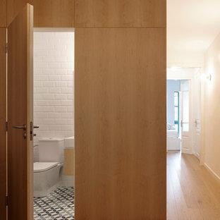 Cette image montre un WC et toilettes méditerranéen de taille moyenne avec un WC séparé, un carrelage blanc, un mur blanc, un sol en carrelage de céramique, un sol bleu, un placard à porte plane, des portes de placard en bois clair, un carrelage métro et un plan vasque.