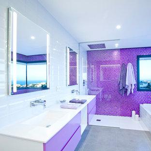 Imagen de aseo contemporáneo con puertas de armario violetas, suelo gris, encimeras blancas, armarios con paneles lisos, paredes multicolor y lavabo integrado