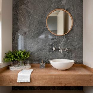 Imagen de aseo escandinavo, de tamaño medio, con armarios abiertos, puertas de armario de madera oscura, baldosas y/o azulejos grises, baldosas y/o azulejos de porcelana, lavabo sobreencimera, encimera de madera, encimeras marrones y paredes blancas