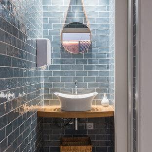 Kleine Nordische Gästetoilette mit blauer Wandfarbe, braunem Holzboden, Aufsatzwaschbecken, Waschtisch aus Holz, blauen Fliesen, Keramikfliesen und brauner Waschtischplatte in Barcelona