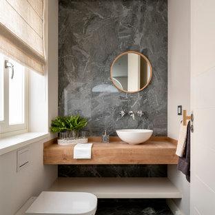 ビルバオの中くらいの北欧スタイルのおしゃれなトイレ・洗面所 (オープンシェルフ、淡色木目調キャビネット、壁掛け式トイレ、グレーのタイル、磁器タイル、ベージュの壁、磁器タイルの床、ベッセル式洗面器、木製洗面台、グレーの床、ブラウンの洗面カウンター) の写真