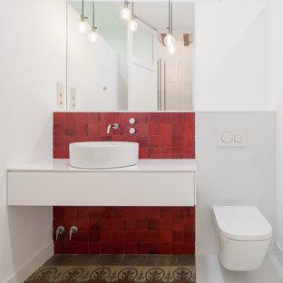 バルセロナの中くらいの地中海スタイルのおしゃれなトイレ・洗面所 (フラットパネル扉のキャビネット、白いキャビネット、壁掛け式トイレ、赤いタイル、白い壁、ベッセル式洗面器、モザイクタイル、マルチカラーの床) の写真