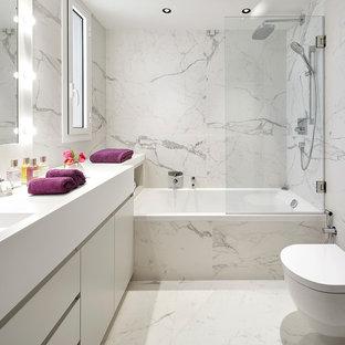 Modelo de aseo contemporáneo con armarios con paneles lisos, puertas de armario blancas, baldosas y/o azulejos blancos, paredes blancas, lavabo integrado, suelo blanco, encimeras blancas y sanitario de pared