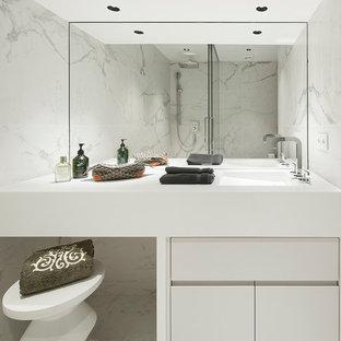 Imagen de aseo contemporáneo con armarios con paneles lisos, puertas de armario blancas, baldosas y/o azulejos blancos, paredes blancas, lavabo integrado, encimeras blancas, baldosas y/o azulejos de mármol, suelo de mármol y suelo blanco