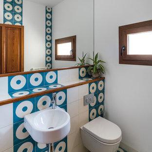 Modelo de aseo actual, pequeño, con sanitario de pared, baldosas y/o azulejos azules, baldosas y/o azulejos blancos, paredes blancas, lavabo suspendido y baldosas y/o azulejos de cerámica