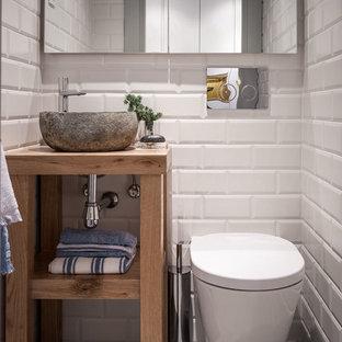 Diseño de aseo nórdico, pequeño, con armarios abiertos, puertas de armario de madera oscura, sanitario de pared, baldosas y/o azulejos blancos, paredes blancas, lavabo sobreencimera y suelo gris