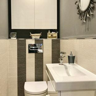 マドリードの小さいコンテンポラリースタイルのおしゃれなトイレ・洗面所 (フラットパネル扉のキャビネット、白いキャビネット、壁掛け式トイレ、グレーのタイル、セラミックタイル、グレーの壁、一体型シンク、グレーの床、木目調タイルの床) の写真