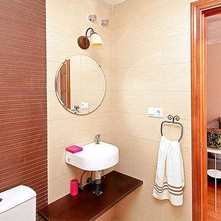 Идея дизайна: маленький туалет в стиле современная классика с бежевыми стенами, подвесной раковиной и столешницей из дерева
