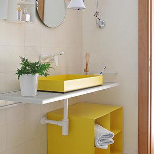 Idée de décoration pour un petit WC et toilettes design avec un carrelage beige, des carreaux de céramique, un mur beige, un sol en carrelage de terre cuite, une vasque, un plan de toilette en acier inoxydable, des portes de placard jaunes et un placard sans porte.