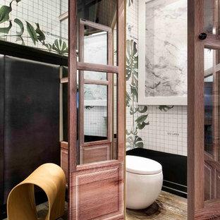 Inspiration pour un petit WC et toilettes ethnique avec un WC à poser, un mur multicolore, un sol en bois brun et un lavabo de ferme.
