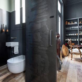Imagen de aseo industrial, de tamaño medio, con sanitario de pared, paredes grises, suelo de madera en tonos medios y lavabo suspendido