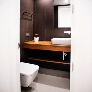 Ispirazione per un piccolo bagno di servizio contemporaneo con nessun'anta, ante in legno scuro, WC sospeso, pareti nere, pavimento con piastrelle in ceramica e lavabo a bacinella