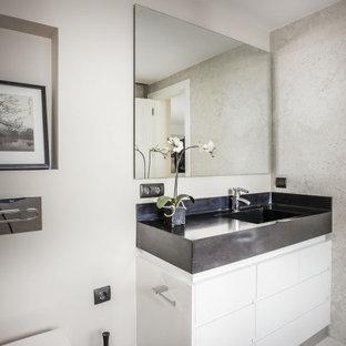 Foto de aseo contemporáneo con armarios con paneles lisos, puertas de armario blancas, sanitario de pared, paredes blancas, suelo gris y encimeras negras