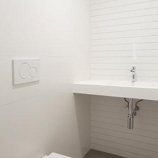 Diseño de aseo moderno, pequeño, con sanitario de pared, baldosas y/o azulejos grises, baldosas y/o azulejos de cerámica, paredes blancas, suelo de baldosas de cerámica, lavabo suspendido, encimera de acrílico, suelo gris y encimeras blancas