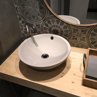 Cette photo montre un petit WC et toilettes industriel avec un placard sans porte, des portes de placard grises, un WC séparé, un carrelage bleu, des carreaux de béton, un mur gris, béton au sol, une vasque, un plan de toilette en bois, un sol gris et un plan de toilette beige.