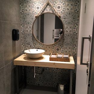 Idee per un bagno di servizio industriale di medie dimensioni con pareti grigie, pavimento in cemento, pavimento grigio, nessun'anta, ante grigie, WC a due pezzi, piastrelle verdi, piastrelle di cemento, lavabo a bacinella, top in legno e top beige
