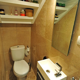 This is an example of a small transitional powder room in Madrid with furniture-like cabinets, dark wood cabinets, an integrated sink and a two-piece toilet.