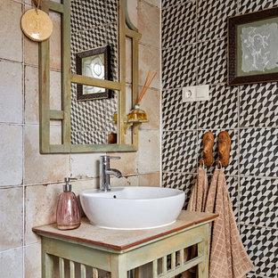 Medelhavsstil inredning av ett litet beige beige toalett, med ett fristående handfat, möbel-liknande, skåp i slitet trä, beige kakel, svart och vit kakel och träbänkskiva
