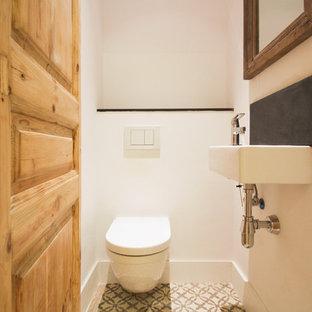 Exemple d'un petit WC et toilettes scandinave avec un WC suspendu, un mur blanc, un sol en carrelage de céramique et un lavabo suspendu.