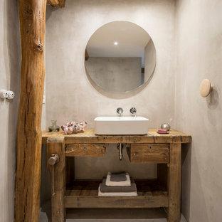 Imagen de aseo rústico con armarios tipo mueble, puertas de armario de madera oscura, paredes grises, suelo de cemento, lavabo sobreencimera, encimera de madera y suelo gris