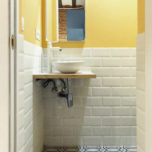 Esempio di un piccolo bagno di servizio scandinavo con pareti gialle, pavimento con piastrelle in ceramica, lavabo sospeso, top in legno e pavimento multicolore