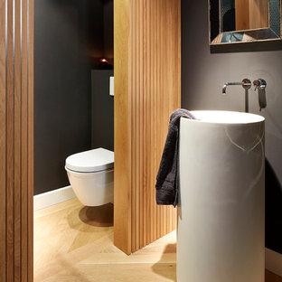 Cette photo montre un petit WC et toilettes tendance avec un WC suspendu, un mur noir, un sol en bois clair et un lavabo de ferme.