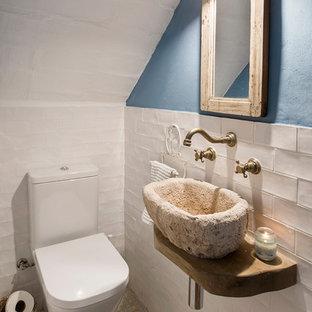 Imagen de aseo mediterráneo, pequeño, con sanitario de dos piezas, lavabo sobreencimera, paredes azules, suelo de azulejos de cemento y suelo multicolor