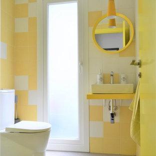 Inspiration pour un WC et toilettes nordique avec un carrelage jaune, des carreaux de céramique, un mur jaune, un sol en carrelage de céramique, une vasque, un plan de toilette en bois, un sol gris et un plan de toilette jaune.